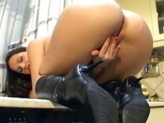 Breasty playgirl apropos leather boots masturbates in a catch kitchen